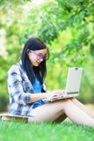 Muchacha adolescente con el ordenador portátil Imagen de archivo