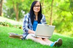 Muchacha adolescente con el ordenador portátil Fotos de archivo
