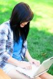 Muchacha adolescente con el ordenador portátil Fotografía de archivo libre de regalías