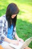 Muchacha adolescente con el ordenador portátil Fotos de archivo libres de regalías