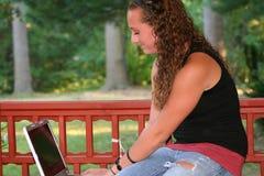 Muchacha adolescente con el ordenador portátil al aire libre Imagen de archivo libre de regalías