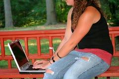 Muchacha adolescente con el ordenador portátil al aire libre Fotos de archivo