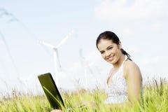 Muchacha adolescente con el ordenador portátil al lado de la turbina de viento. Fotos de archivo libres de regalías