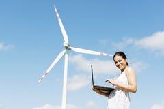 Muchacha adolescente con el ordenador portátil al lado de la turbina de viento. Fotos de archivo
