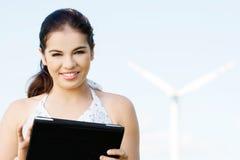 Muchacha adolescente con el ordenador portátil al lado de la turbina de viento. Imagen de archivo