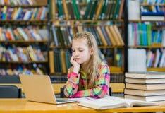 Muchacha adolescente con el ordenador portátil en biblioteca Fotos de archivo