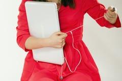 Muchacha adolescente con el ordenador portátil y los auriculares Imagen de archivo libre de regalías