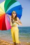 Muchacha adolescente con el paraguas en la costa Foto de archivo