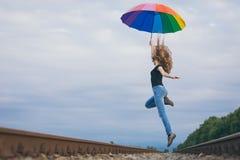 Muchacha adolescente con el paraguas que salta en el ferrocarril en el tiempo del día Imagenes de archivo