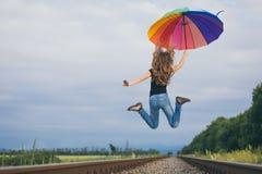 Muchacha adolescente con el paraguas que salta en el ferrocarril en el tiempo del día Fotos de archivo libres de regalías