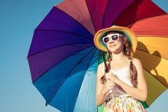 Muchacha adolescente con el paraguas que se coloca en la playa en el tiempo del día Foto de archivo
