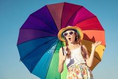 Muchacha adolescente con el paraguas que se coloca en la playa en el tiempo del día Fotografía de archivo