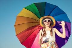 Muchacha adolescente con el paraguas que se coloca en la playa en el tiempo del día Fotos de archivo