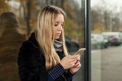 Muchacha adolescente con el pelo largo con un smartphone Fotografía de archivo