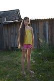 Muchacha adolescente con el pelo largo en la yarda del campo, pueblo ruso Fotos de archivo libres de regalías