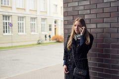 Muchacha adolescente con el pelo largo que habla en el teléfono al aire libre en capa Imagen de archivo