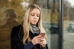 Muchacha adolescente con el pelo largo que mira en el smartphone Fotos de archivo libres de regalías