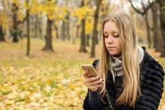 Muchacha adolescente con el pelo largo que se sienta en el parque en la caída con un smartphone Fotografía de archivo