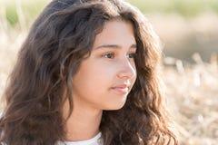Muchacha adolescente con el pelo oscuro rizado en la naturaleza Fotografía de archivo