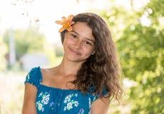 Muchacha adolescente con el pelo oscuro rizado en la naturaleza Imagen de archivo