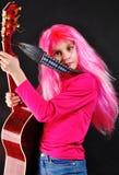 Muchacha adolescente con el pelo rosado que toca la guitarra Imagenes de archivo
