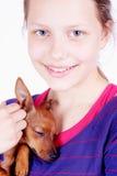 Muchacha adolescente con el perro en sus manos, primer Imagenes de archivo