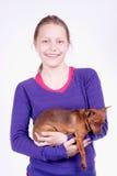 Muchacha adolescente con el perro en sus manos, tiro del estudio Imagen de archivo
