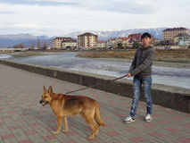 Muchacha adolescente con el perro que camina en el 'promenade' del río Imagen de archivo libre de regalías