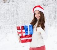 Muchacha adolescente con el sombrero de santa y las cajas de regalo rojas que muestran los pulgares para arriba en bosque del inv Foto de archivo