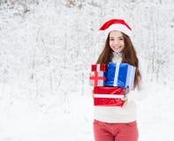 Muchacha adolescente con el sombrero de santa y las cajas de regalo rojas que se colocan en bosque del invierno Fotografía de archivo