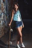 Muchacha adolescente con el tablero del patín Imagen de archivo libre de regalías