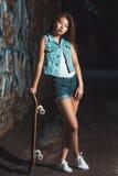 Muchacha adolescente con el tablero del patín, forma de vida urbana Fotos de archivo