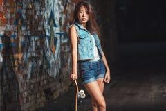 Muchacha adolescente con el tablero del patín, forma de vida urbana Imagenes de archivo