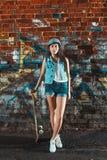 Muchacha adolescente con el tablero del patín, forma de vida urbana Fotografía de archivo