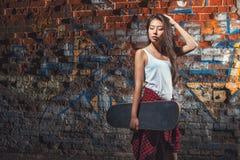 Muchacha adolescente con el tablero del patín, forma de vida urbana Foto de archivo