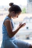 Muchacha adolescente con el teléfono elegante Imagen de archivo