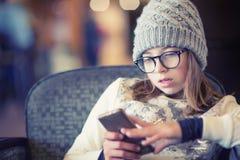 Muchacha adolescente con el teléfono elegante Muchacha que envía un mensaje de texto en una multitud Fotos de archivo