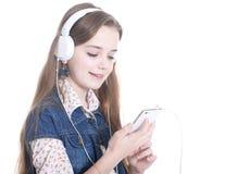 Muchacha adolescente con el teléfono y los auriculares Imagen de archivo
