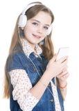 Muchacha adolescente con el teléfono y los auriculares Fotos de archivo
