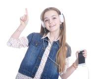 Muchacha adolescente con el teléfono y los auriculares Foto de archivo libre de regalías