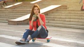 Muchacha adolescente con fresco con sabor a fruta y el monopatín Foto de archivo libre de regalías