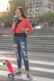 Muchacha adolescente con fresco con sabor a fruta y el monopatín Fotografía de archivo