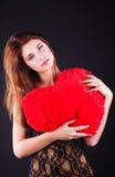 Muchacha adolescente con la almohada del corazón Imágenes de archivo libres de regalías