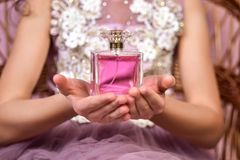 Muchacha adolescente con la botella rosada del parfume en sus manos Foto de archivo