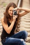 Muchacha adolescente con la cámara en los ferrocarriles. Imagenes de archivo