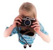 Muchacha adolescente con la cámara retra en un fondo blanco Imagen de archivo