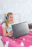 Muchacha adolescente con la computadora portátil Imagen de archivo libre de regalías