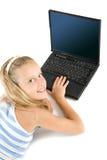 Muchacha adolescente con la computadora portátil aislada en blanco Fotografía de archivo