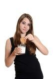 Muchacha adolescente con la galleta dunked en leche Imágenes de archivo libres de regalías