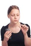 Muchacha adolescente con la píldora y agua en vidrio Fotos de archivo libres de regalías